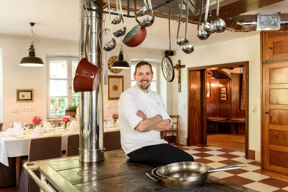 Chef de cuisine of Brauereigasthof Aying, Mario Huggler, sitting on a traditional wamser ofen